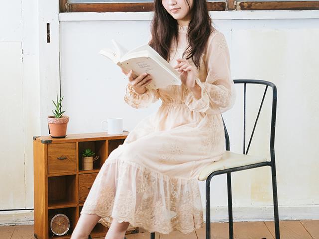 椅子に座って本を読んでいる女性