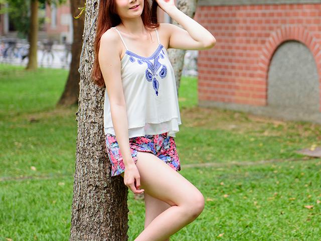木にもたれて片足をあげている女性