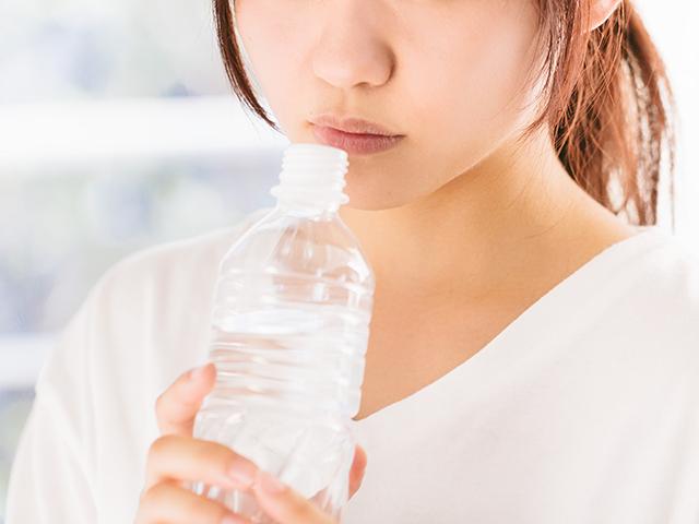 ペットボトルの水を飲もうとしている女性
