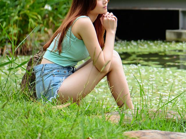 草の茂みでしゃがんでいるタンクトップの女性
