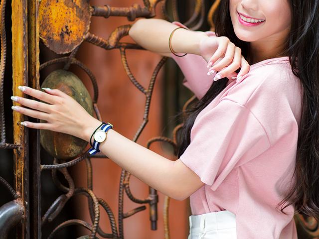 腕時計つけたピンク色のシャツの女性