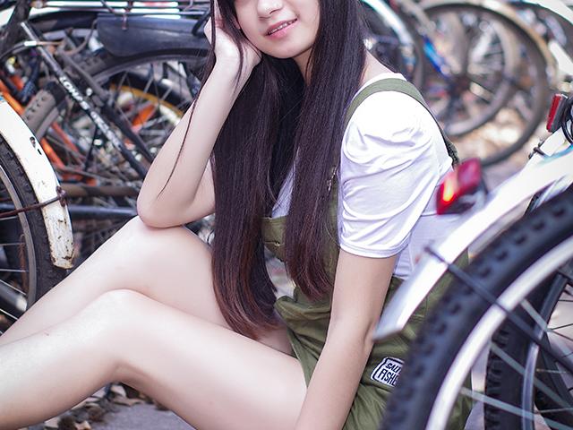 自転車置場で座り込んでいる女性