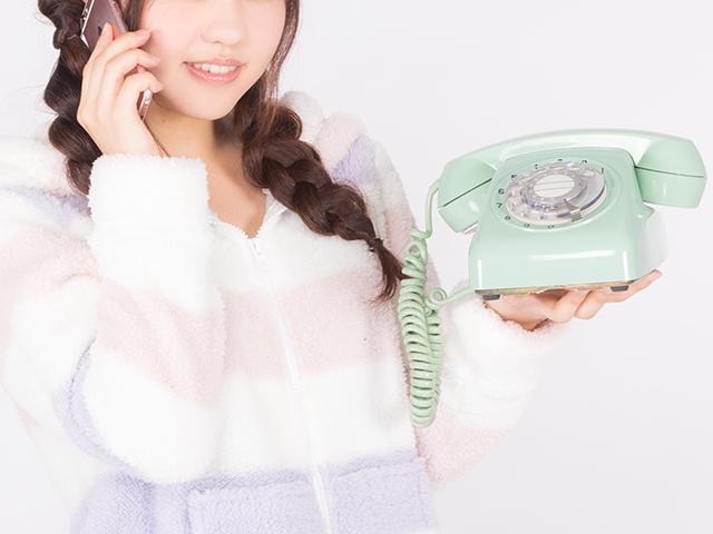 旧式の電話を使っている女性