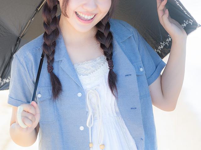 日傘をさしながら微笑んでいる女性
