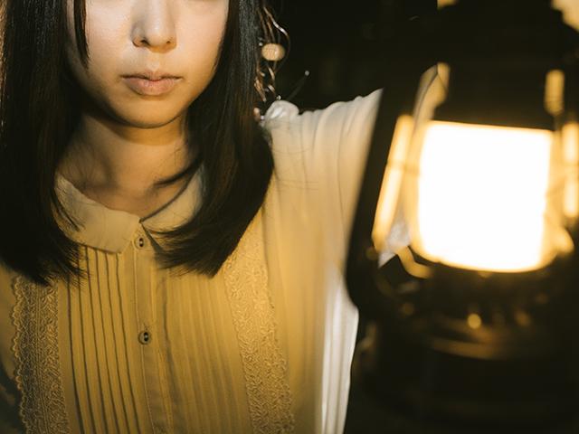 ランプをかざしている女性