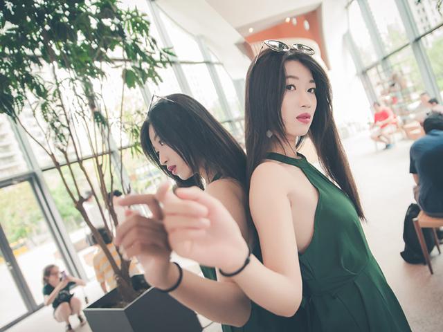 緑のワンピースをきて鏡にもたれる女性