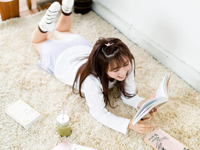 絨毯の上で寝転んで本を読んでいる女性