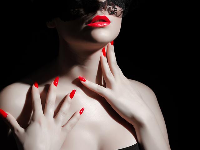赤い口紅とネイルの女性
