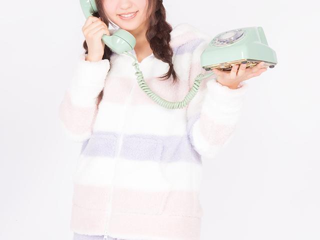 旧式のダイヤル電話で話している女性