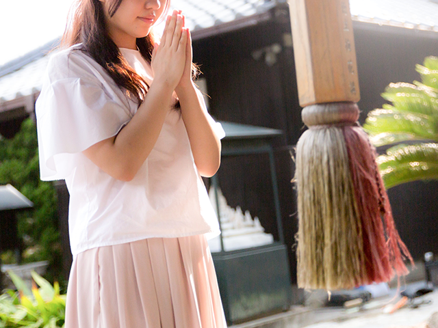 神社で参拝している女性