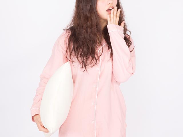 枕抱えてあくびしているパジャマ姿の女性