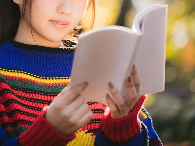 野外で本を読んでいるカラフルなセーターの女性