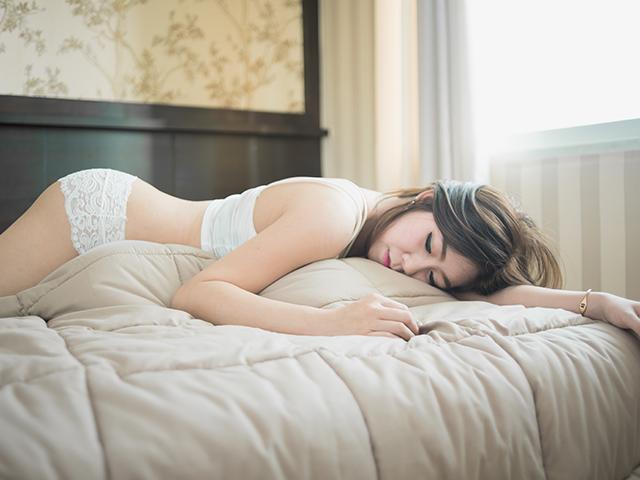 ベッドにうつぶせで眠る女性