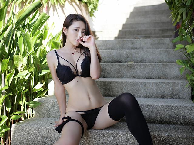 下着姿で外の階段に座り込む女性