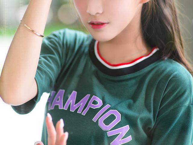 髪をかきあげている緑色のシャツの女性