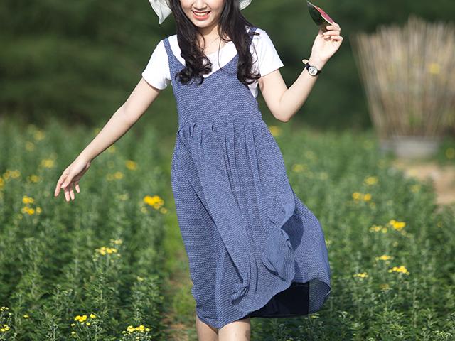 花畑を歩く白い帽子の女性
