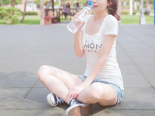 地べたに座って水を飲んでいる女性