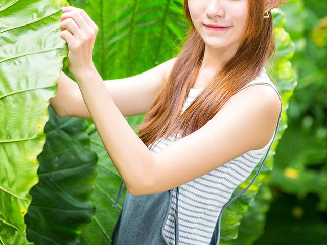 大きな葉っぱをつまんでいる女性
