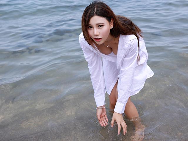 白シャツで海を楽しむ女性