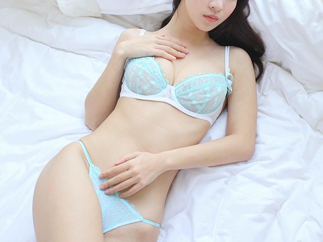 水色の下着でベッドに横たわる女性