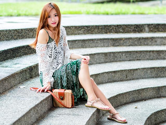 階段に座っている緑のワンピースを着た女性
