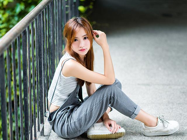 ラフな格好で柵の前に座りこんでいる女の子
