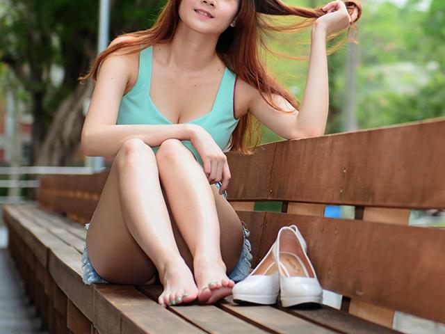 長いベンチに裸足で横向きに三角座りをする女性