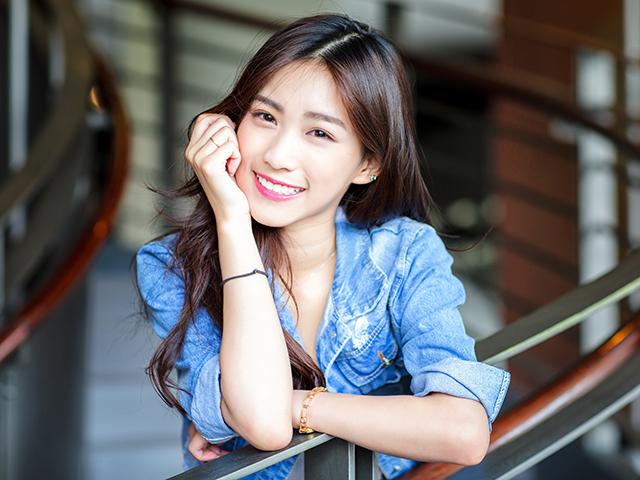 柵に肘を置き笑顔を向ける女性