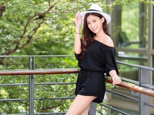柵にもたれかかりハット帽を抑える女性