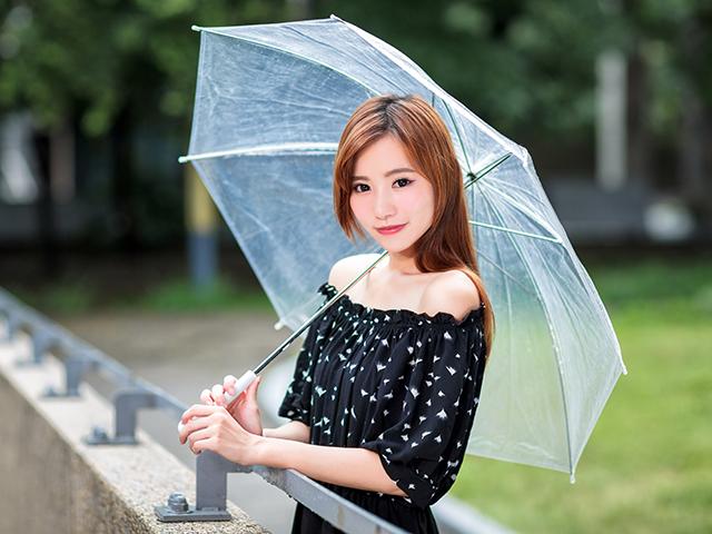 晴れの日にビニール傘をさしている女性
