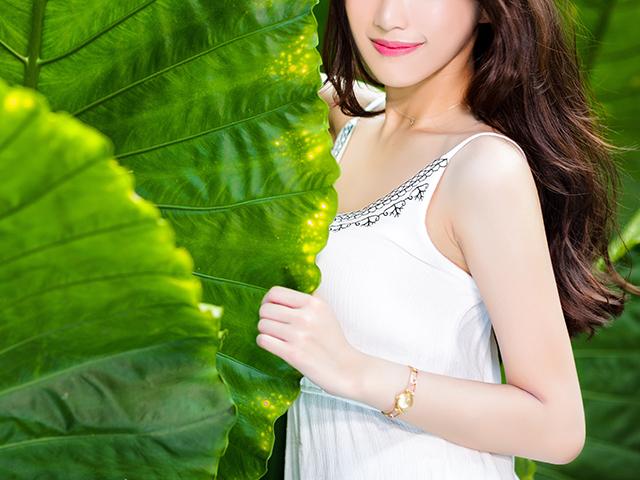 大きな葉っぱの中に見を隠そうとしている女性