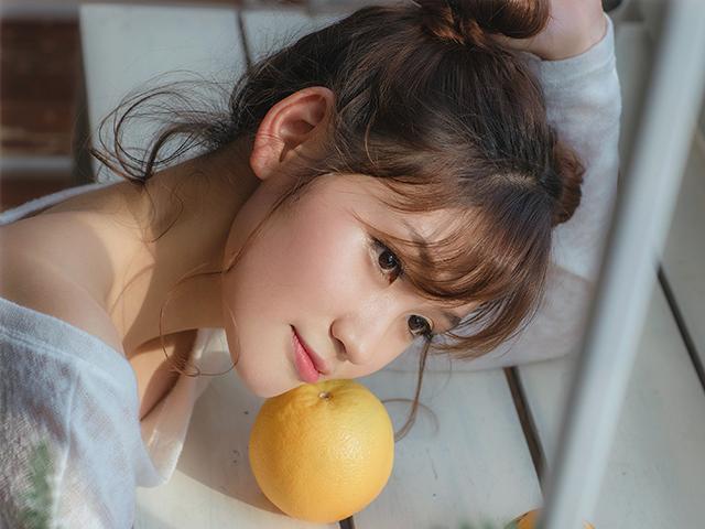 グレープフルーツに顎を置いて遠くを見つめる女性