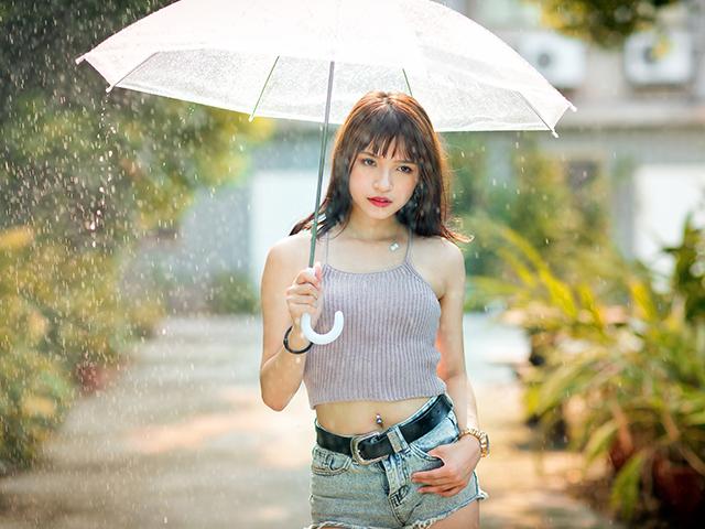 大粒の雨の中傘をしてたたずむ女性