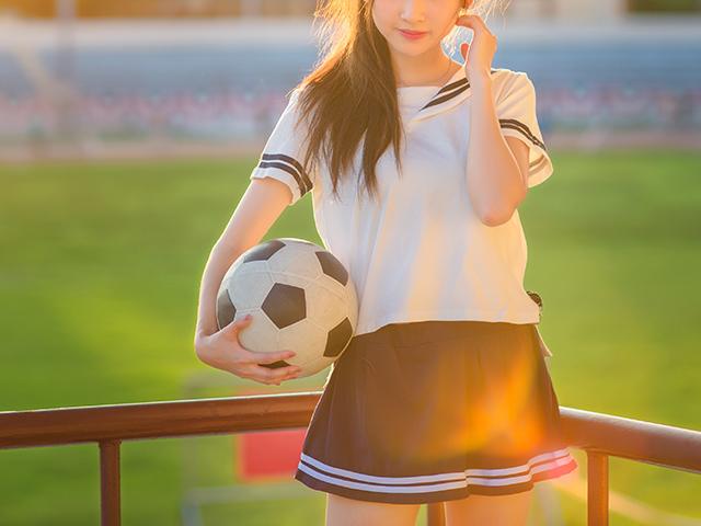 球技場でサッカーボールをもちながら夕日に当たる女の子