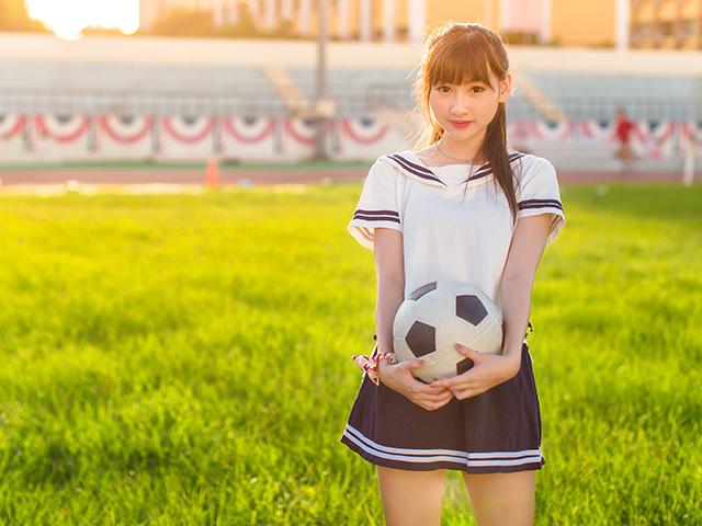 サッカーボールをもって芝生にたたずむ女の子