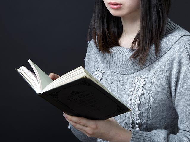 本を呼んでいるグレーのニットを着た女性