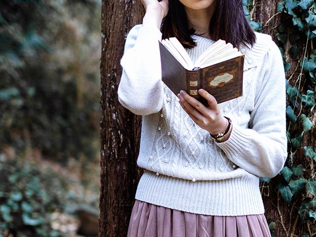 木の側で読書をしている女性