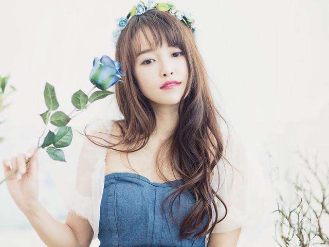 花かんむりを頭に被り、青いバラを手に持った女性