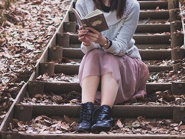 枯葉にまみれた階段で読書している女性