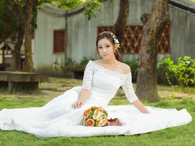 白いドレスを着て芝生の上に座り込む女性