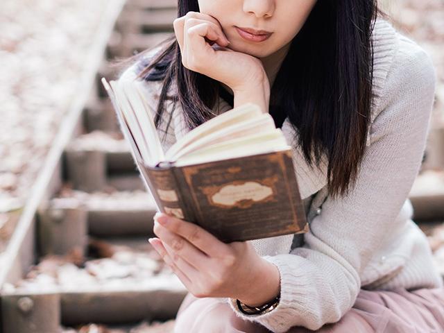 物語を想像しながら階段で本を読む女性