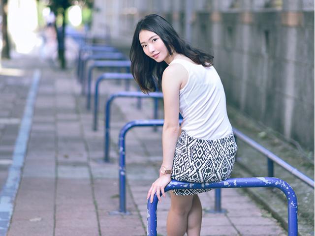 塗装の剥げた青い防護柵に腰掛けながら後ろを振り返る、幾何学模様柄のスカートを履いた女性