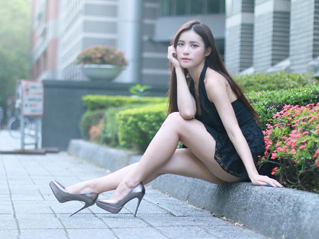 花壇の縁に腰掛けながらどこかを見つめる黒いドレスを着たハーフ風の女性