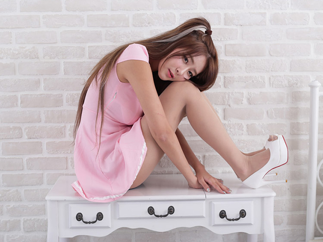 白いテーブルの上に座り、頬に膝を当てながらどこかを見つめる女性