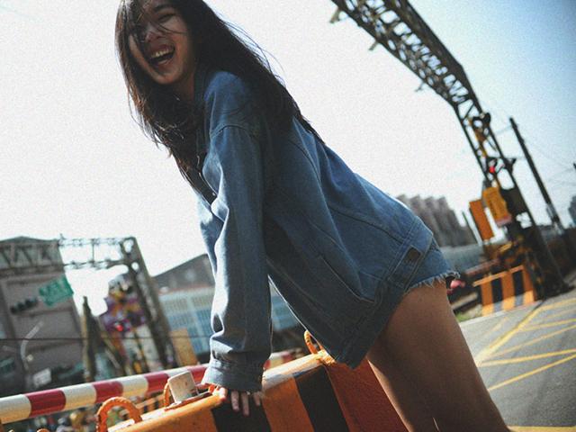 一見裸ワイシャツにも見えかねないけれどもデニムのホットパンツを履いて笑う女性