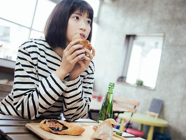 お店で瓶ジュースとパンを食べる女の子