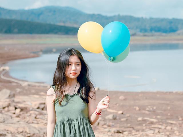 草木も生えない荒れた湖のほとりで風船を持ち歩く女性