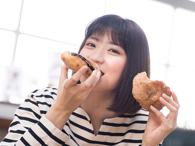 両手にパンを持っておいしそうに頬張る女性