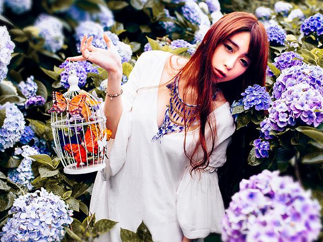 紫陽花に囲まれて虫かごを持っている女性