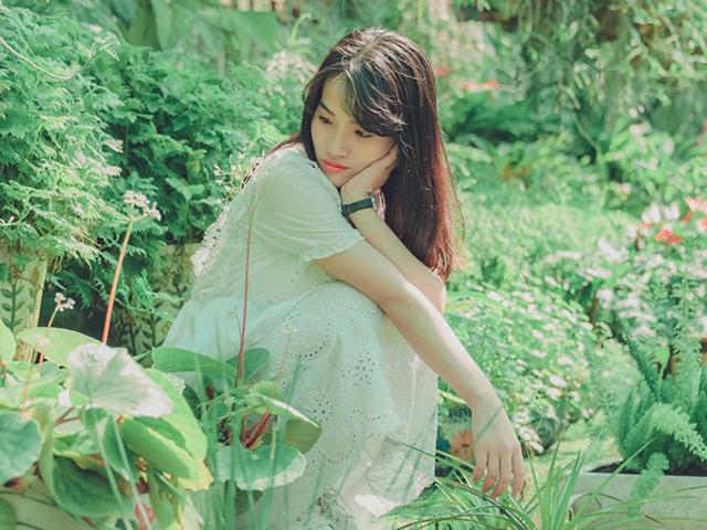 植物と一体化するのを諦め、近くにある植物を羨ましそうに見つめる女性